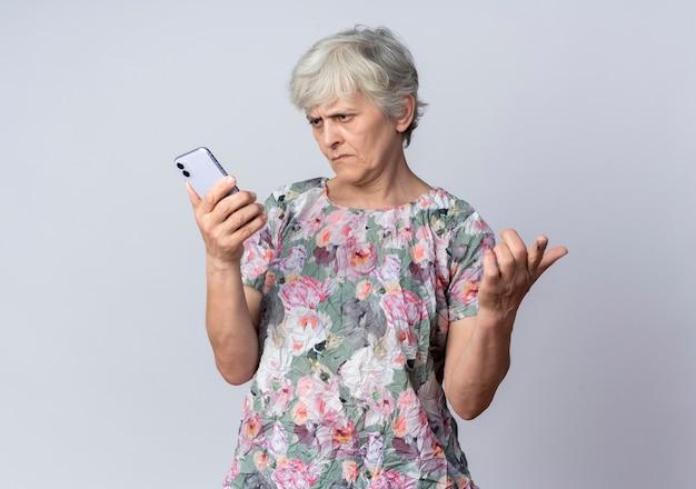 Niezadowolona starsza kobieta trzyma i patrzy na telefon na białym tle na białej ścianie