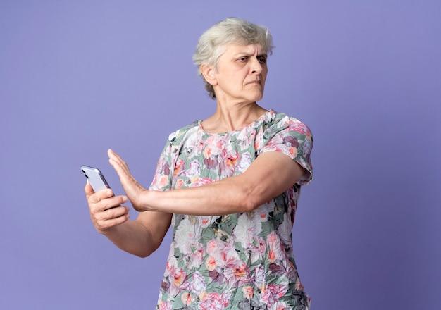 Niezadowolona starsza kobieta trzyma i udaje, że popycha telefon patrząc na bok odizolowany na fioletowej ścianie