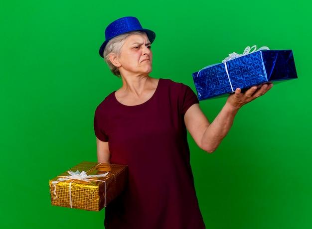 Niezadowolona starsza kobieta w kapeluszu imprezowym trzyma i patrzy na pudełka na prezenty na zielono