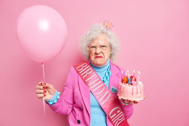 Niezadowolona starsza pani z kręconymi włosami świętuje urodziny nosi modne ubrania i biżuterię pozuje z napompowanym balonem smaczne ciasto wygląda z zrzędliwym wyrazem