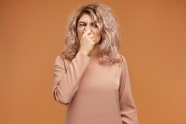 Niezadowolona, stylowa młoda kobieta wymiotuje z powodu nieznośnego smrodu brudnych skarpet. zabawna dziewczyna wykrzywiając nos i szczypiąc, wstrzymując oddech