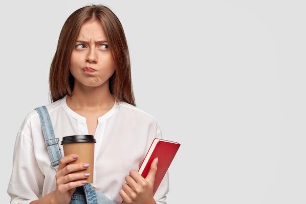 Niezadowolona urocza studentka czuje się niezadowolona z uczenia się przez cały czas, trzyma filiżankę kawy na wynos i książkę, myśli o odpoczynku, ma ponury wyraz twarzy