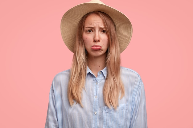 Niezadowolona urocza turystka w eleganckim kapeluszu, torebka na dolnej wardze, czuje się samotna lub maltretowana, nie ma towarzysza podróży