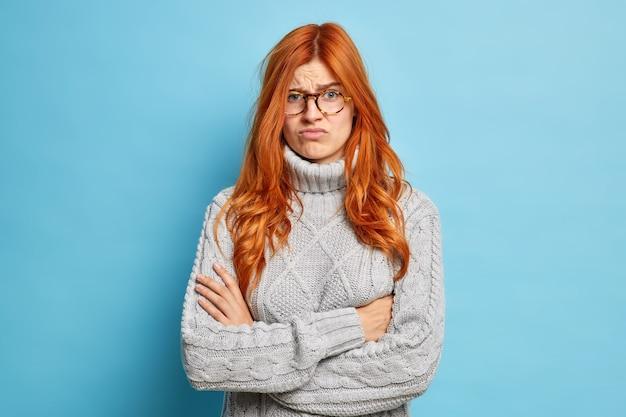 Niezadowolona, wściekła kobieta marszczy brwi, twarz trzyma założone ręce i niezadowolona z czegoś, co słyszy głupią informację, stoi w dzianinowym swetrze