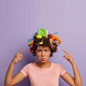 Niezadowolona wściekła kobieta pozuje ze śmieciami we włosach