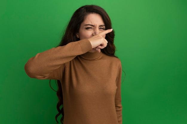 Niezadowolona z zamkniętymi oczami młoda piękna dziewczyna wycierająca nos palcem na zielonej ścianie z miejscem na kopię