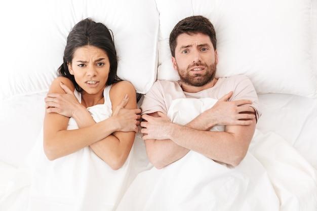 Niezadowolona, zamarznięta młoda, kochająca się para leży w łóżku chowając się pod kocem