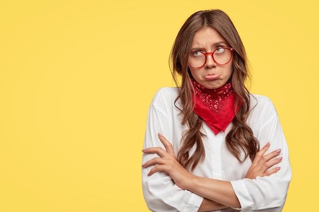 Niezadowolona zamyślona młoda kobieta rasy kaukaskiej torebki dolną wargę, trzyma ręce skrzyżowane, nosi okulary, ubrana w modne ubrania, odizolowana na żółtej ścianie z wolną przestrzenią po lewej stronie