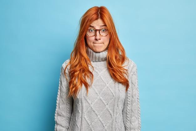 Niezadowolona zdziwiona ruda młoda kobieta zaciska usta i wygląda na zawstydzoną, ma zszokowany wyraz twarzy ubrany w sweter i okulary.