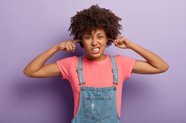 Niezadowolona zirytowana kręcona kobieta trzyma palce wskazujące w otworach uszu, ignoruje irytujący dźwięk, zaciska zęby, ubrana w swobodny strój, zatyka uszy