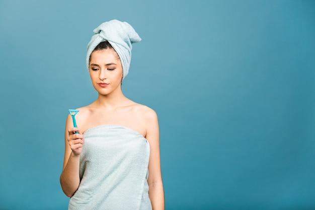 Niezadowolona zła kobieta przeciw goleniu, trzyma brzytwę w dłoni, wspiera depilację woskiem, pozuje półnaga, pokazuje nagie ramiona