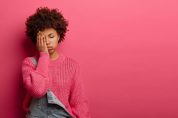 Niezadowolona zmęczona kobieta zasłania twarz ze zmęczenia