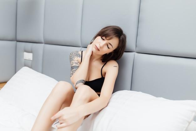 Niezadowolona, zmęczona młoda piękna kobieta budzi się z bólem szyi rano w swoim łóżku