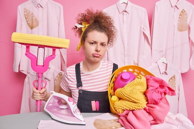 Niezadowolona znudzona pokojówka nie chce robić prac domowych trzyma mop do czyszczenia podłogi w pokoju stoi w pobliżu deski do prasowania z koszem na pranie ubranym niedbale ma ponury wyraz twarzy. prace domowe