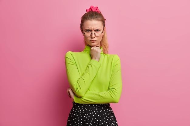 Niezadowolona zrzędliwa dziewczyna wygląda na obrażoną, trzymając rękę pod brodą, nie zgadza się z czyjąś opinią