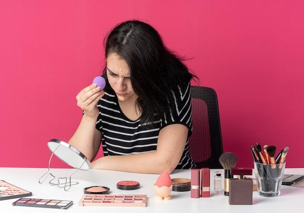 Niezadowolone, patrząc w lustro, młoda piękna dziewczyna siedzi przy stole z narzędziami do makijażu, nakładającymi krem tonujący z gąbką na białym tle na różowym tle