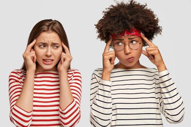 Niezadowolone, sfrustrowane dziewczyny trzymają palce wskazujące na skroniach, starają się przypomnieć sobie informacje