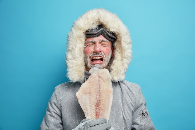Niezadowolony arktyczny człowiek pokryty szronem podczas surowego mroźnego mroźnego dnia i pogody utrzymuje zamrożone ryby w północnych częściach. mężczyźni eskimosi w odzieży wierzchniej.