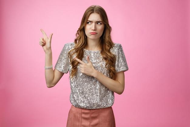Niezadowolony, arogancki snobistyczny, bogaty glamour dziewczyna wyglądająca na niezadowoloną, kulącą się, wskazującą w lewo na bok...
