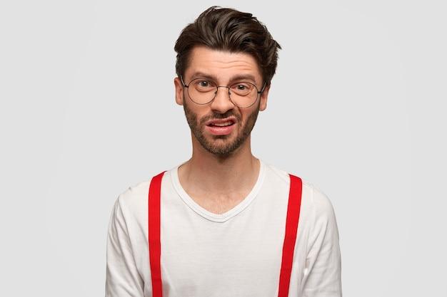 Niezadowolony, atrakcyjny młody hipster mężczyzna ma zdziwiony wyraz twarzy, marszczy brwi, patrzy z niechęcią, zauważa coś nieprzyjemnego, nosi białą koszulę z czerwonymi szelkami. koncepcja mimiki.