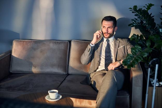Niezadowolony biznesmen na kanapie słucha wiadomości przez telefon