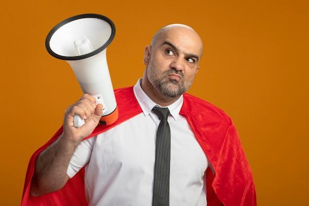 Niezadowolony biznesmen super bohater w czerwonej pelerynie trzymając megafon patrząc na bok stojąc nad pomarańczową ścianą