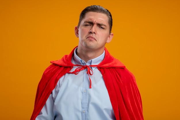 Niezadowolony biznesmen super bohatera w czerwonej pelerynie ze smutnym wyrazem twarzy stojącej nad pomarańczową ścianą