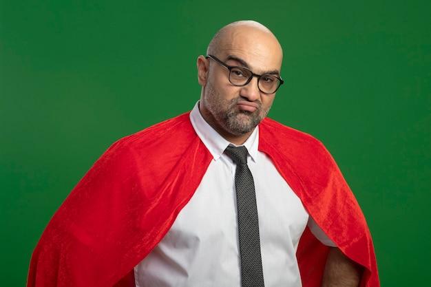 Niezadowolony biznesmen superbohatera w czerwonej pelerynie i okularach
