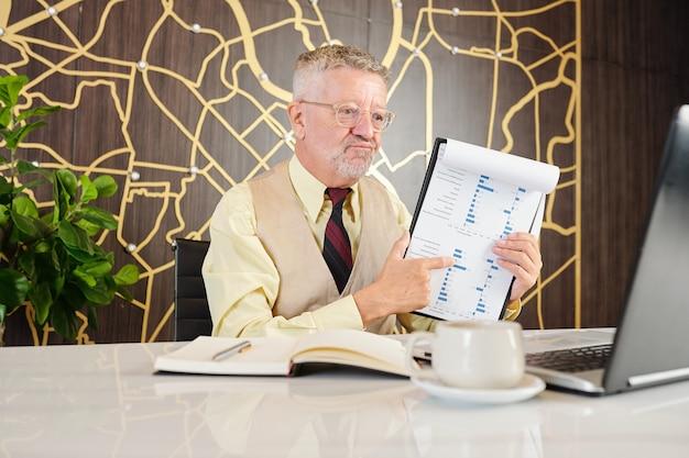 Niezadowolony biznesmen w wieku menedżer działu rozmów wideo i pokazujący raport sprzedaży z kiepskimi danymi