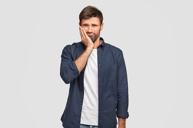 Niezadowolony brodacz trzyma rękę na policzku, marszczy brwi z niezadowoleniem, słyszy negatywne wiadomości, nie chce iść do pracy, nosi modną ciemnoniebieską koszulę, stoi samotnie pod białą ścianą