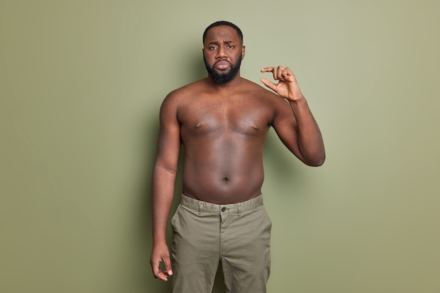 Niezadowolony brodaty afroamerykanin pozuje z nagim torsem pokazuje maleńkie gesty przedstawiające bardzo małe przedmioty na ciemnozielonej ścianie