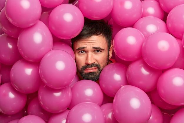 Niezadowolony, brodaty europejczyk, zmęczony po aranżacji przyjęcia urodzinowego, pozuje wokół wielu różowych balonów