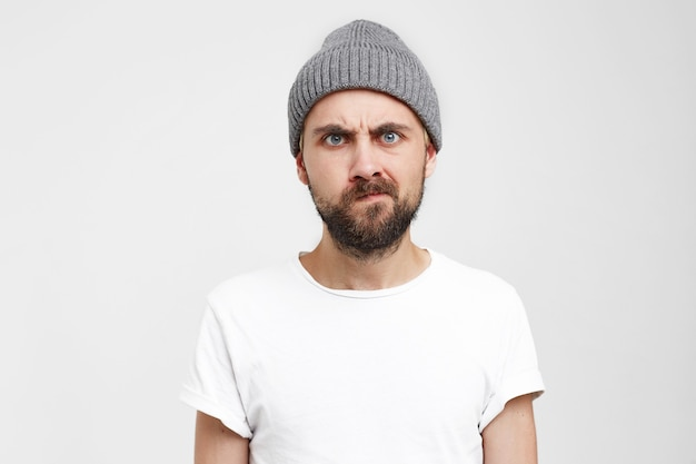 Niezadowolony brodaty mężczyzna w szarym kapeluszu, brwi zmarszczone, oczy agresywne, jeden kącik ust ściągnięty