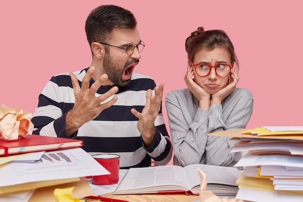 Niezadowolony, brodaty młody nauczyciel gestykuluje ze złością, krzyczy na leniwego ucznia, który nie jest gotowy do pracy w domu