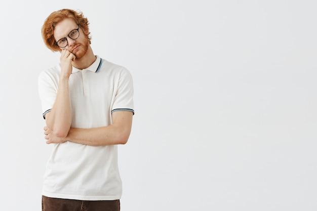 Niezadowolony brodaty rudy facet pozuje przy białej ścianie w okularach