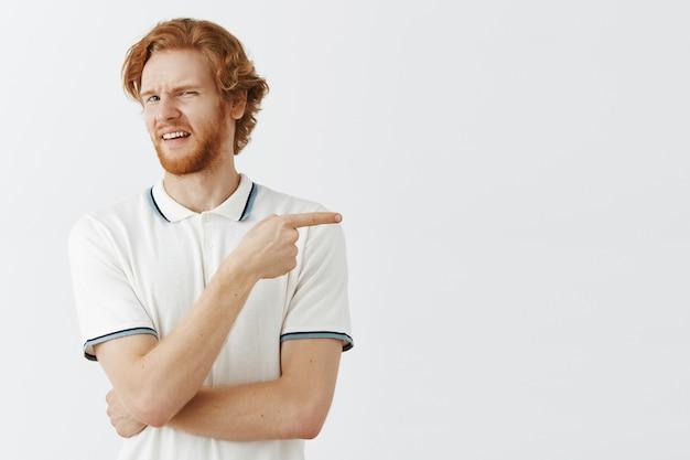 Niezadowolony brodaty rudy facet pozuje przy białej ścianie