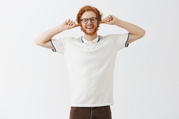 Niezadowolony brodaty rudy facet pozuje w okularach przy białej ścianie