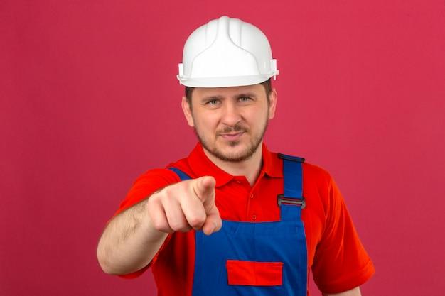 Niezadowolony budowniczy mężczyzna ubrany w mundur budowlany i hełm ochronny, wskazujący palcem na aparat na izolowanej różowej ścianie