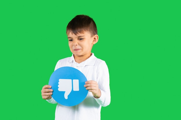 Niezadowolony chłopiec malucha trzymający kciuk w dół znak