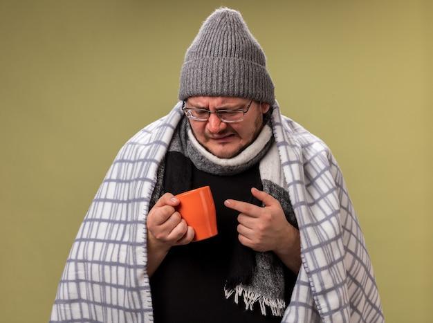 Niezadowolony, chory mężczyzna w średnim wieku, ubrany w zimową czapkę i szalik owinięty w kratę i patrzący na filiżankę herbaty