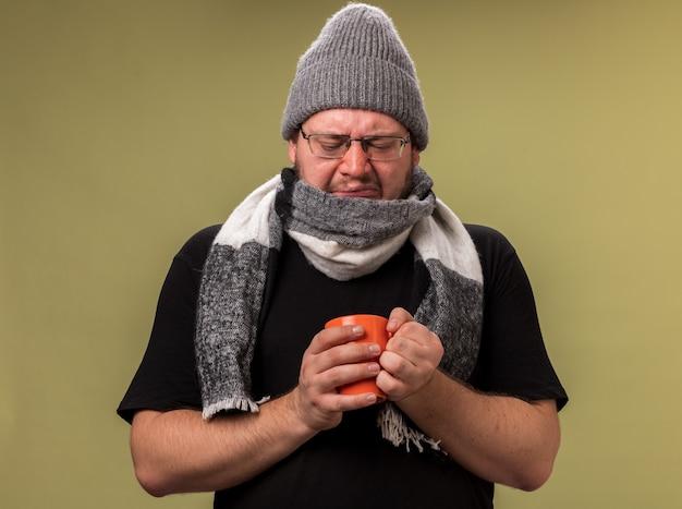 Niezadowolony, chory mężczyzna w średnim wieku, ubrany w zimową czapkę i szalik, trzymający i patrzący na filiżankę herbaty odizolowaną na oliwkowozielonej ścianie