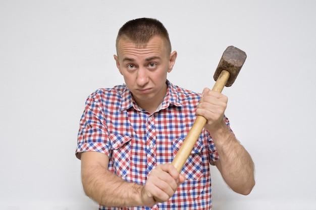 Niezadowolony człowiek z młotem na białej ścianie. koncepcja pracy