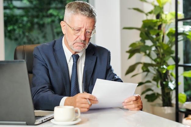 Niezadowolony dojrzały biznesmen pije kawę i czyta kontrakt podczas pracy przy biurku