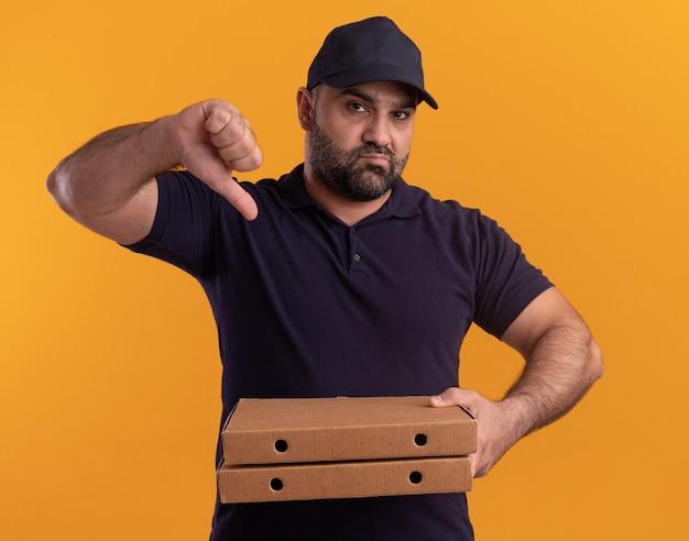 Niezadowolony doręczyciel w średnim wieku w mundurze i czapce trzymający pudełka po pizzy pokazujący kciuk w dół na żółtej ścianie