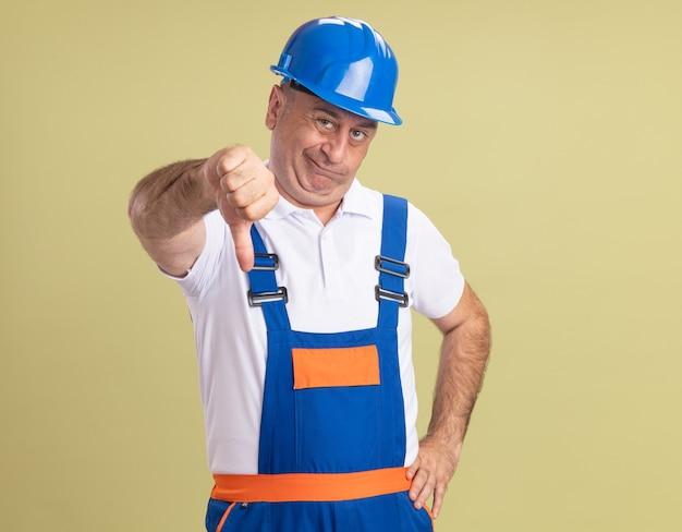Niezadowolony dorosły budowniczy mężczyzna w mundurze kciuki w dół na białym tle na oliwkowej ścianie