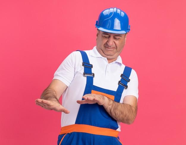 Niezadowolony dorosły budowniczy mężczyzna w mundurze trzyma ręce otwarte na białym tle na różowej ścianie