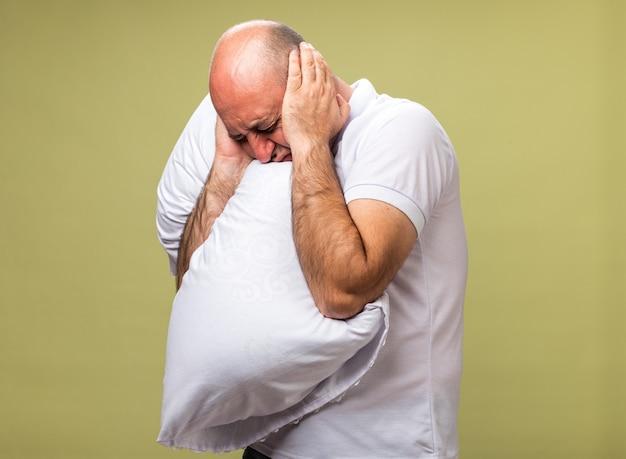 Niezadowolony dorosły chory kaukaski mężczyzna zamyka uszy rękami, trzymając poduszkę odizolowaną na oliwkowej ścianie z miejsca na kopię