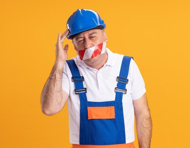Niezadowolony dorosły kaukaski mężczyzna budowniczy w mundurze zakrywa usta taśmą klejącą i kładzie rękę na głowie na pomarańczowo