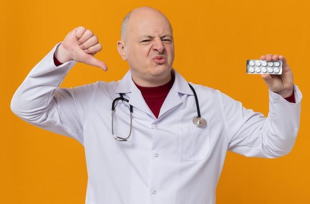 Niezadowolony dorosły mężczyzna w mundurze lekarza ze stetoskopem trzyma blister z lekiem i kciuk w dół
