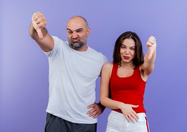 Niezadowolony dorosły para mężczyzna trzyma rękę na talii i kobieta trzyma rękę na brzuchu, zarówno patrząc, jak i pokazując kciuki w dół